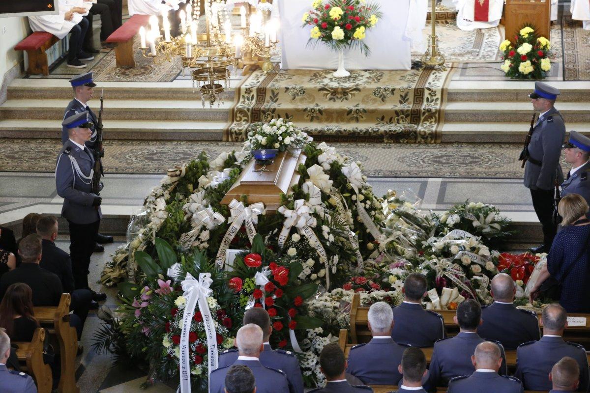 Wnętrze kościoła, trumna z ciałem Wnętrze kościoła w środku zdjęcia  trumna z ciałem sierż. szt. Tomasza Iwańca otoczona wieńcami.  Po obu stronach zdjęcia policjanci uczestniczący w pogrzebie.