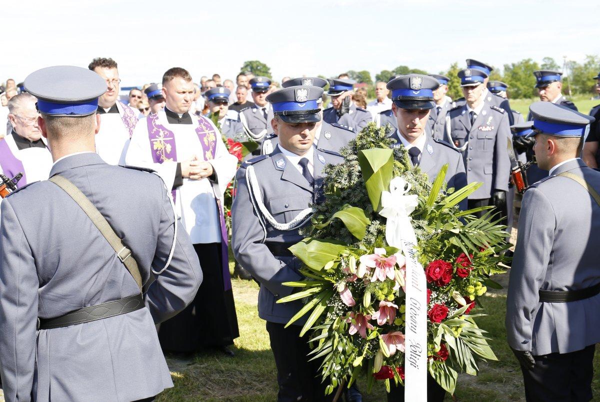 Policjanci kładą wieniec na grobie sierż. szt. Tomasza Iwańca.