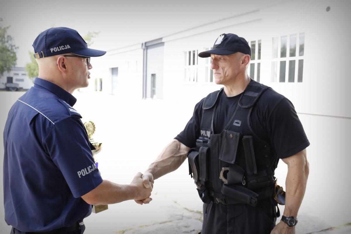 Zastępca Komendanta Wojewódzkiego Policji w Lublinie insp. Radek Bąchór wręcza puchar policjantowi.