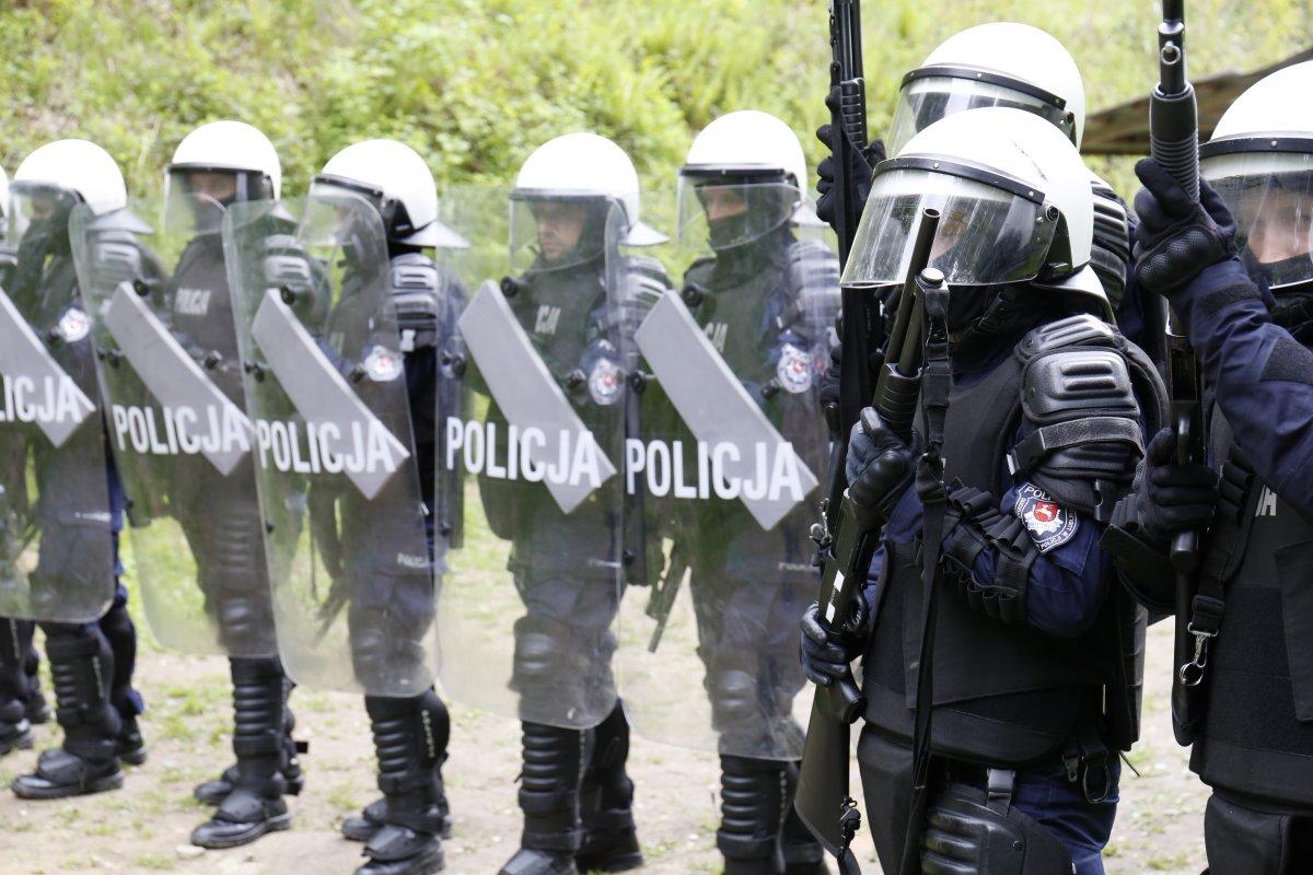 Policjanci z Oddziału Prewencji z tarczami w kaskach ćwiczą na poligonie.