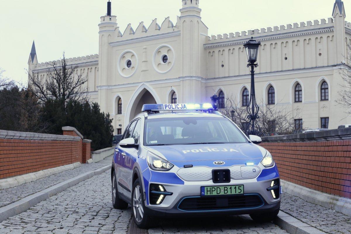 Oznakowany radiowóz policji wtle Zamek Lubelski.