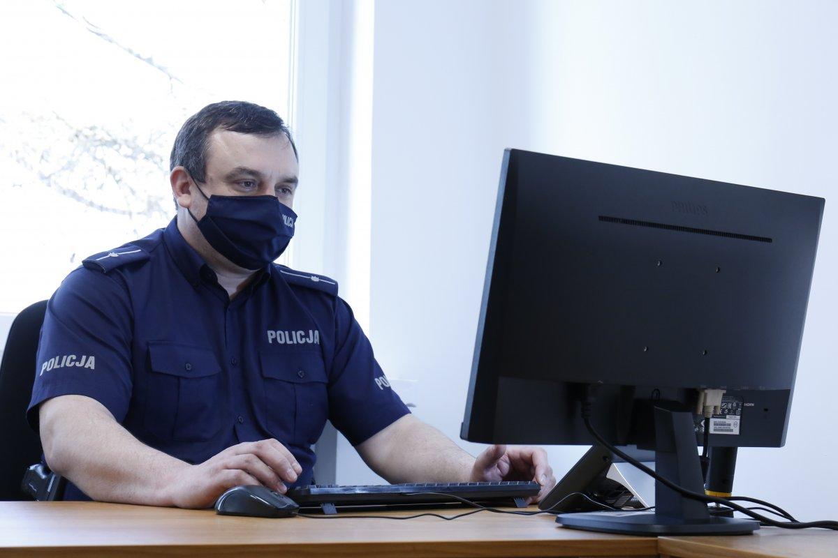 młodszy aspirant Wojciech Skalski przy biurku z założona maseczką patrzy w monitor komputera.