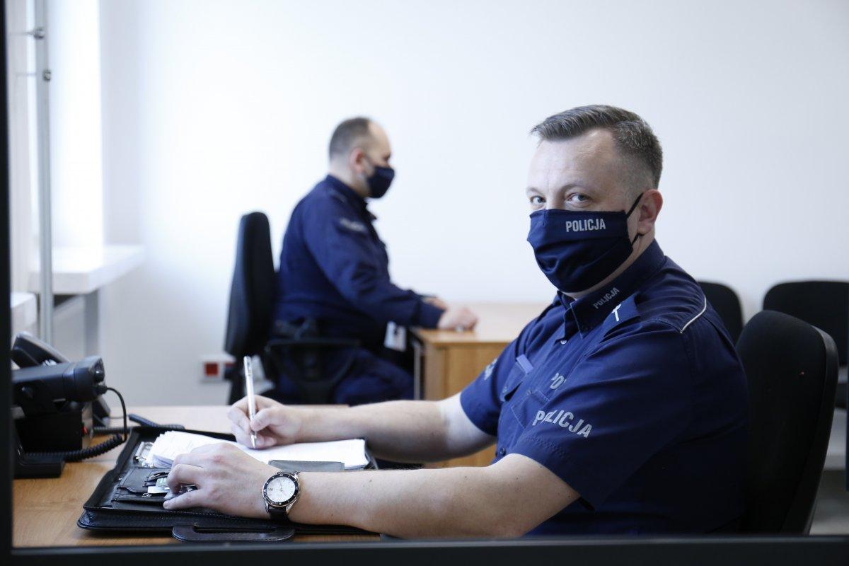 W pierwszym planie policjant na dyżure zwrócony do widza. W drugim planie inny funkcjonariusz pracuje przy biurku.