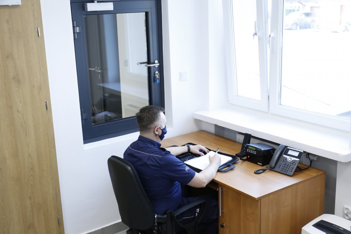 Pomieszczenie dyżurka policjant w granatowym mundurze pracuje przy biurku.