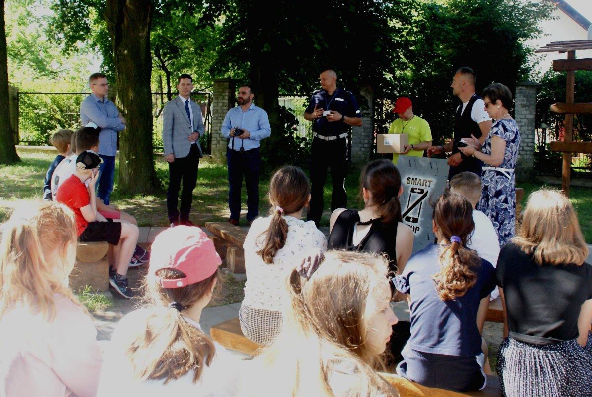 pogadanka z uczniami przed szkołą z udziałem policjanta i innych osób z instytucji publicznych