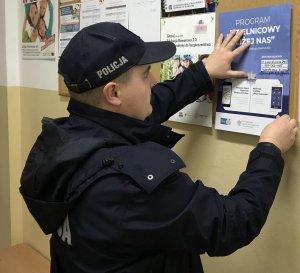 Policjant wiesza plakat
