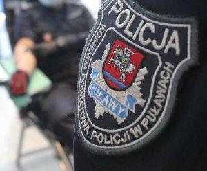 napis komenda powiatowa policji w Puławach na mundurze w tle policjant oddający krew